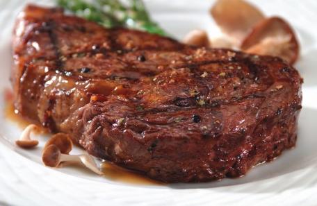 Právě ugrilovaný šťavnatý rib-eye steak na bílém talíři.